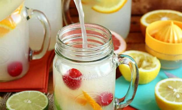 pitcher of lemonade pouring into a glass with citrus fruit